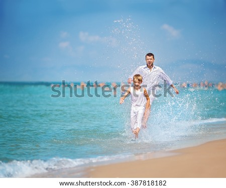 Happy father with son playing together, running and jumping on a beach on a sunny hot summer day