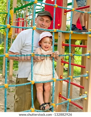 happy father with toddler  on playing field in summer - stock photo