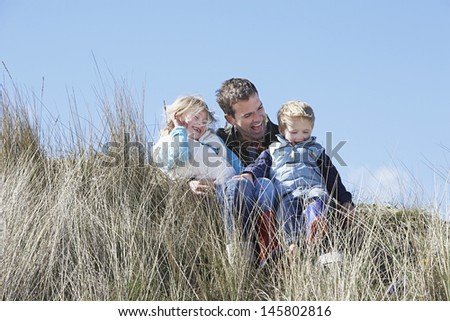 Happy father with two children sitting in long grass outdoors - stock photo