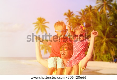 happy father with two kids on shoulders having fun at tropical beach - stock photo