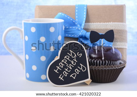 Happy Fathers Day cupcake gift on pale blue and white wood background.  - stock photo