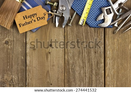 Happy Fathers Day gift tag with top border of tools and ties on a rustic wood background - stock photo