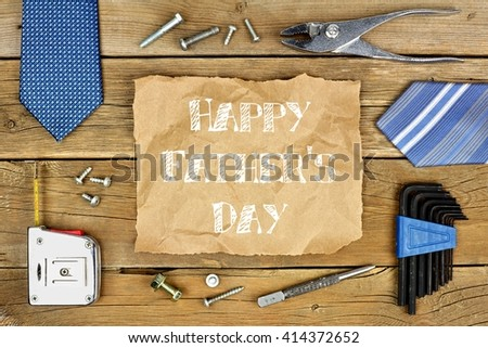 Happy Fathers Day message on rustic paper with frame of tools and ties on a wooden background - stock photo