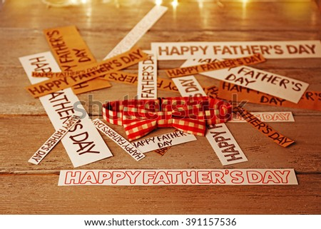 Happy fathers day stickers and bow tie on wooden table