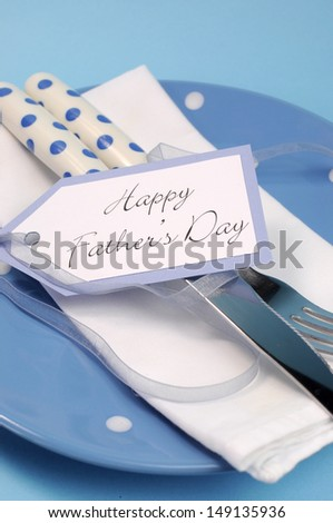 Happy Fathers Day table place setting close up with blue polka dot plate and cutlery with gift tag message greeting. Vertical.