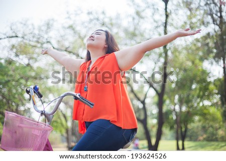Happy fatty asian woman outstretched with bicycle outdoor in a park - stock photo
