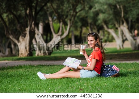 Happy femail tourist is relaxin in park on a grass. Backpack, mail and coffee