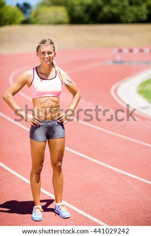 Happy female athlete standing with hand on hip on running track