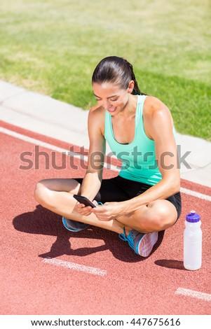 Happy female athlete using mobile phone on running track - stock photo