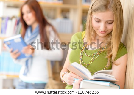 Happy female blonde student at library read books high school - stock photo