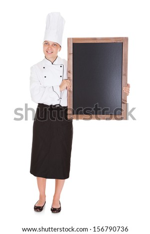 Happy female chef holding blank menu board on white background