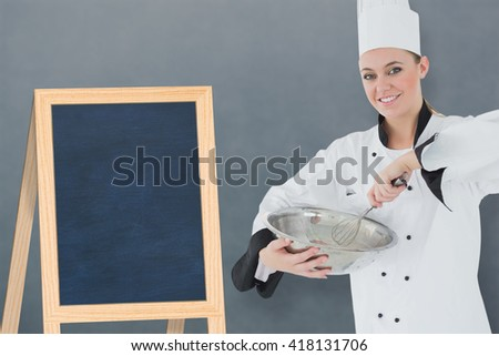 Happy female chef holding wire whisk and mixing bowl against a board in a white background