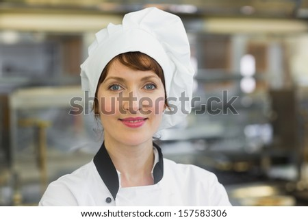 Happy female chef posing in a kitchen smiling at the camera  - stock photo