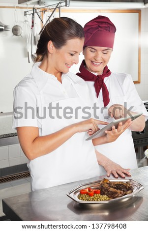 Happy female chefs looking for recipe on a digital tablet while cooking at kitchen