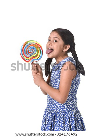 happy female child holding big lollipop candy licking the candy with her tongue in sugar addiction and kid love for sweet concept isolated on white background - stock photo