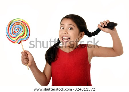 happy female child in red dress holding big lollipop candy pulling her pony tail with crazy funny face expression in sugar addiction and kid love for sweet candy concept isolated on white background - stock photo