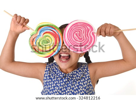 happy female child wearing dress holding two big lollipop in front of her face having fun in sugar addiction and kid love for sweet candy concept isolated on white background - stock photo