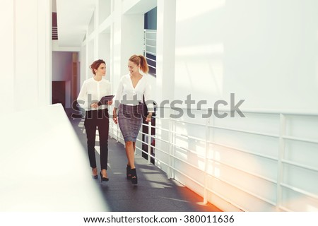 Happy female colleagues planning the schedule of work for next project via digital tablet while walking in office interior, women intelligent lawyers laughing at funny video on touch pad during break - stock photo