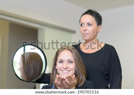 Happy Female Customer In a Salon Sitting In Front a Hairdresser Woman Holding a Round Mirror, Smiling at the Camera After Styling her Hair. - stock photo