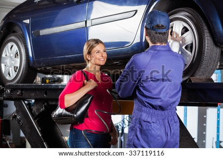 Happy female customer looking at mechanic refilling car tire at garage - stock photo
