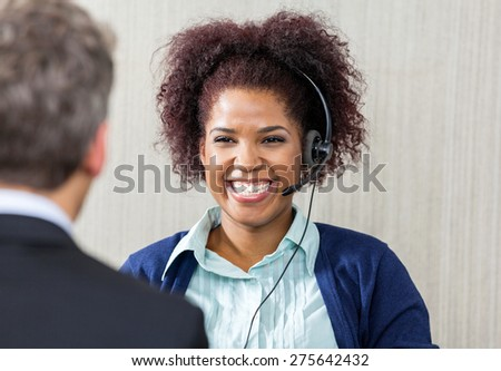 Happy female customer service executive wearing headset while looking at manager in office - stock photo