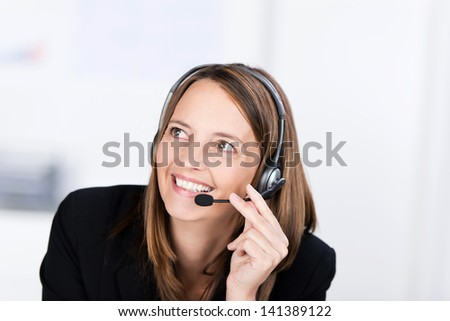 Happy female customer service operator conversing on headset at office