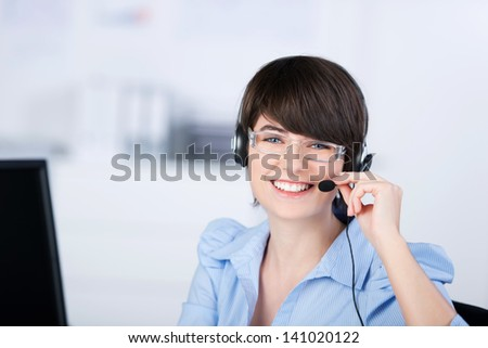 Happy female customer service representative working with headphone and computer