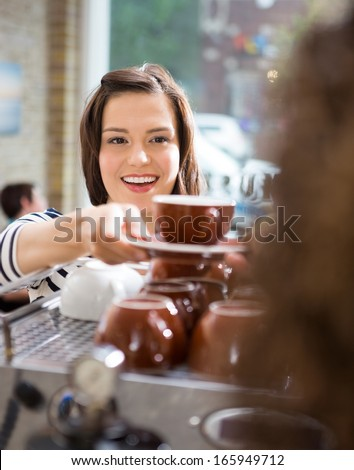 Happy female customer taking coffee from waitress in cafe - stock photo