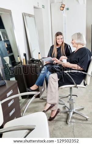 Happy female customers communicating at hair salon - stock photo