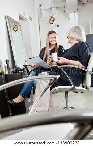 Happy female customers communicating while waiting in hair salon
