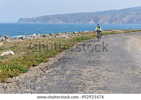 Happy female cyclist  rides a bicycle on the road along the ocean shore  and looking at the camera.