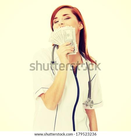Happy  female doctor holding money - stock photo