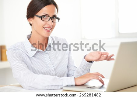 Happy female employee with glasses using the computer while looking at you - stock photo