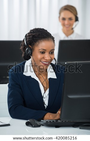 Happy Female Employee With Headset Working On Computer At Desk - stock photo