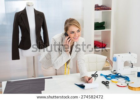 Happy Female Fashion Designer Talking On Cellphone While Writing Note - stock photo
