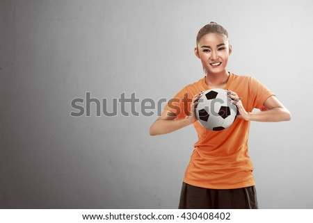 Happy female football fan holding ball over grey background - stock photo