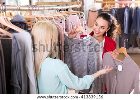 Happy female friends choosing new tops in shop and smiling
