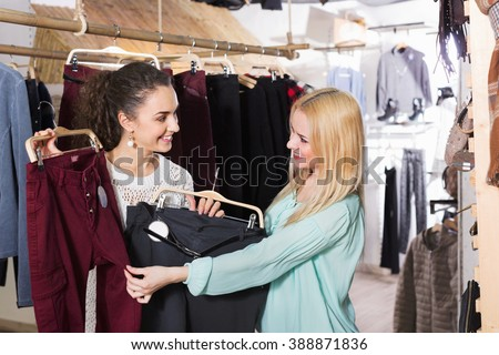 Happy female friends choosing trousers in shop and smiling