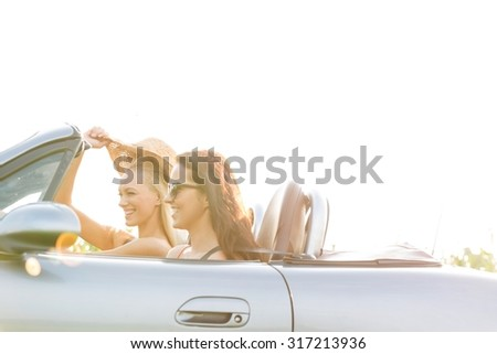Happy female friends enjoying road trip in convertible against clear sky - stock photo
