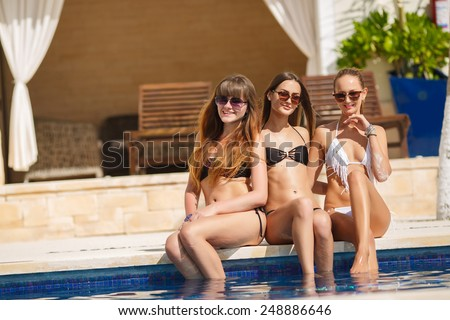 happy female friends enjoying summer near the pool. Sexy young group of women relaxing on deck chair. sexy girl in bikini lying near swimming pool.  - stock photo