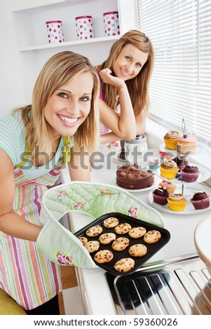 Happy female friends holding cookies in the kitchen at home - stock photo