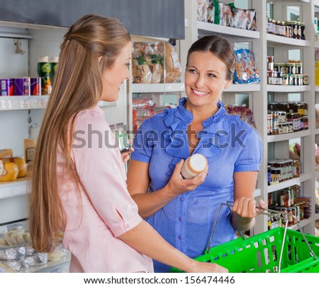 Happy female friends shopping grocery at supermarket - stock photo
