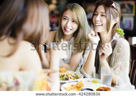 happy female friends sitting and chatting in restaurant