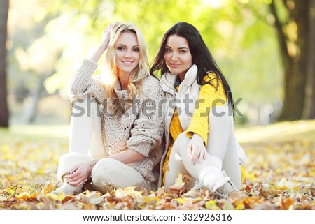 Happy female friends sitting on ground in autumn park - stock photo