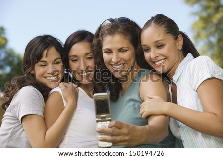 Happy female friends taking self portrait through mobilephone in park - stock photo
