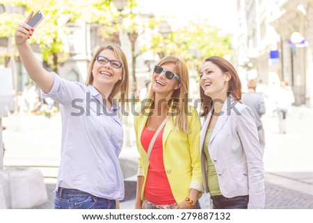 Happy Female Friends Taking Selfie with phone on the street.Friendship Lifestyle.Caucasian urban girl taking photo with mobile. - stock photo