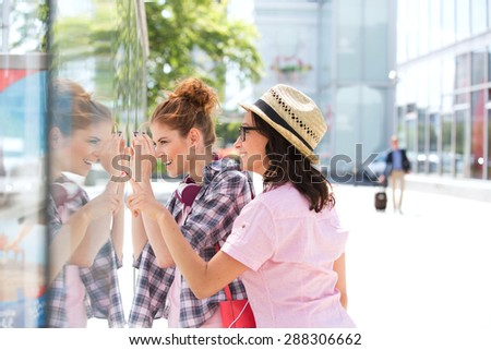 Happy female friends window shopping in city - stock photo