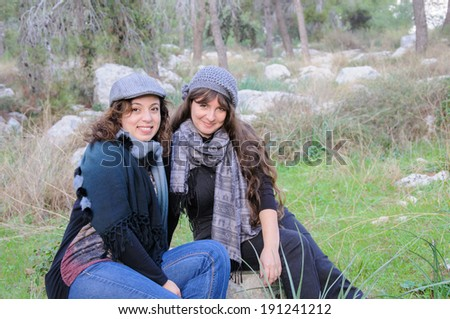 Happy female friends with hats and scarfs in a forest
