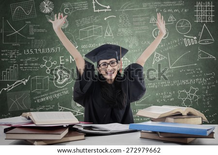 Happy female grad raised her arms in classroom with books and laptop