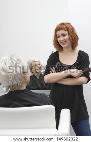 Happy female hair stylist discussing with senior woman in salon - stock photo